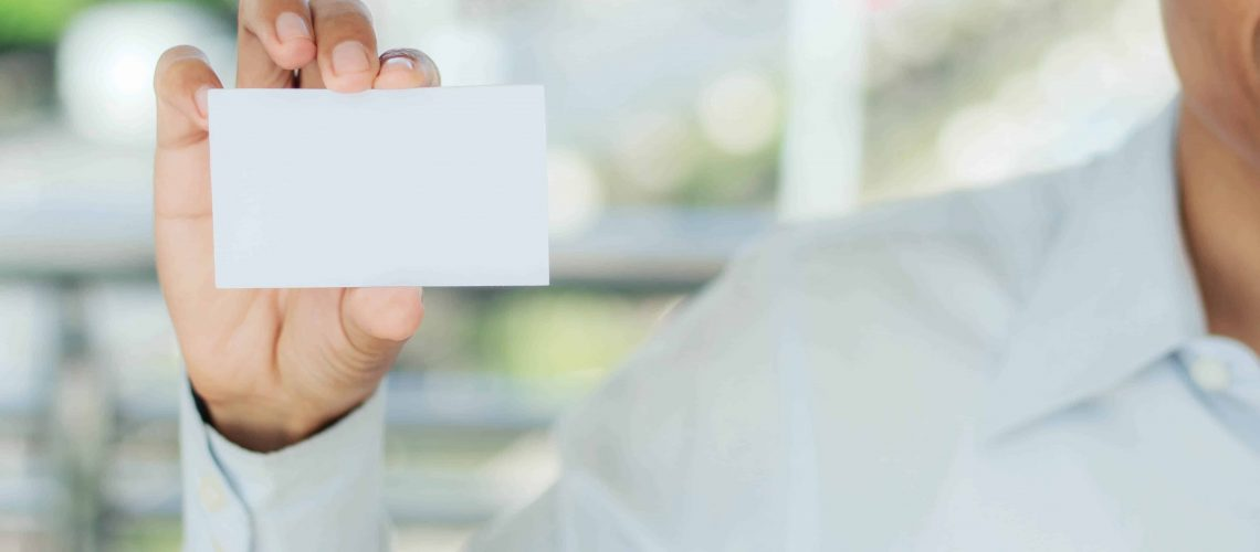 Young man holding a white business card.