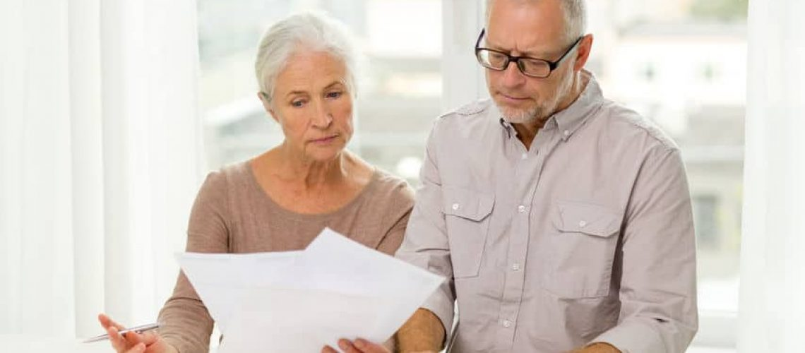 34035075 - family, business, savings, age and people concept - senior couple with papers and calculator at home